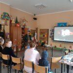 Zdjecie przedstawia bibliotekarza i uczestników w trakcie lekcji bibliotecznej w świetlicy w Paprotach