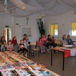 Zdjęcie przedstawia bibliotekarza z uczestnikami lekcji bibliotecznej oraz zbiór książek z kolekcji prywatnej bibliotekarza w świetlicy w Gorzycy