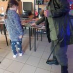 Zdjęcie przedstawia dziecko z bibliotekarzem pokazującym militaria w świetkicy w Paprotach