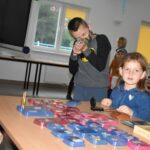 Zdjęcie przedstawia młodych uczestników lekcji bibliotecznej przeglądających militaria w świetlicy w Gorzycy