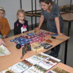 Zdjęcie przedstawia najmłodszych uczestników lekcji bibliotecznej w trakcie oglądania książek i militariów z kolekcji bibliotekarza w świetlicy w Gorzycy