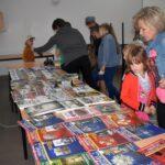 Zdjęcie przedstawia uczestników lekcji bibliotecznej w trakcie przeglądania książek i militariów ze zbiorów prywatnych bibliotekarza w świetlicy w Gorzycy